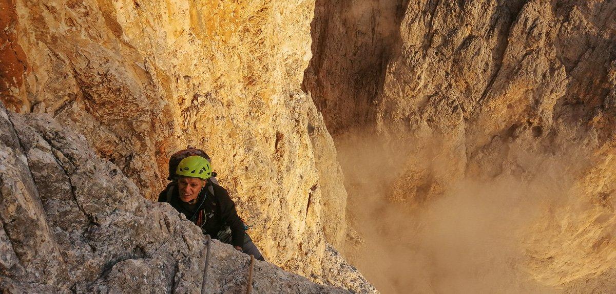 Atmosfera incredibile lungo l'ultimo tiro impegnativo della via. Giacomo arrampica su una roccia dal colore infuocato dal sole che sta per tramontare - Pala di San Martino – Gran Pilastro (Langes-Merlet)